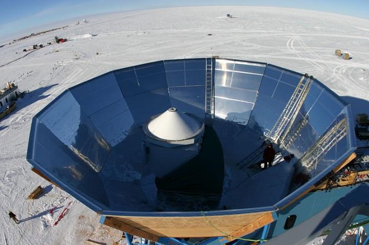 Foto do telescópio QUaD dentro de seu escudo de aterramento. O QUaD consiste de um sistema ótico Cassegrain integrado a base DASI e cercado por um escudo protetor que limita a contaminação do sinal a partir do chão polar embaixo, na temperatura de 200 K. O espelho secundário fica suspenso por um funil branco que é transparente para as frequências de radiação de microondas.