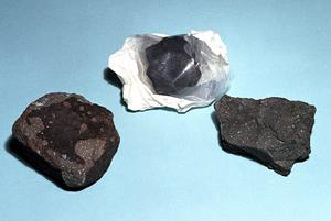 Fragmentos de condritas carbonáceas. Da esquerda para a direita: Allende, Yukon e Murchison.