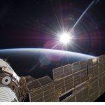 Visão do Sol brilhante, a Terra crescente e a Estação Espacial Internacional