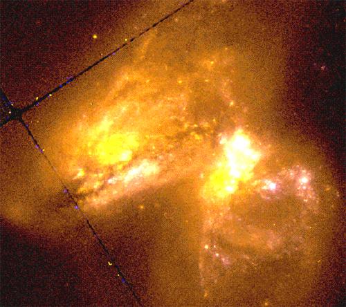Muitas jovens remanescentes de supernovas emitem ondas de radio a partir da galáxia Arp 299 (IC 694), à esquerda. Os núcleos à direita sugerem a presença de grandes aglomerados estelares.