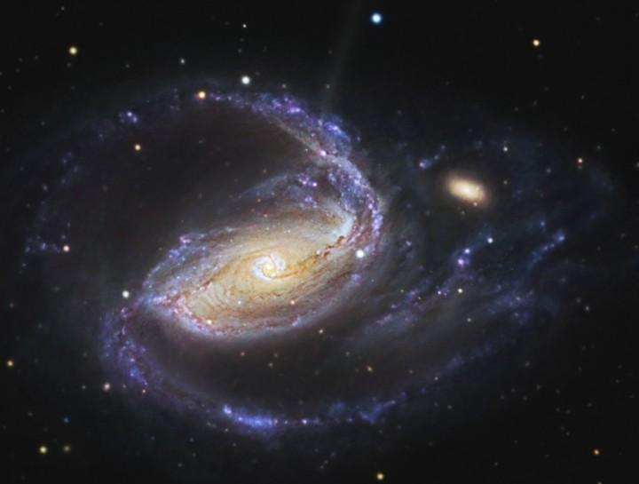 R. Jay GaBany (Cosmotography.com) nos mostra aqui a galáxia Arp 77 sendo 'abraçada' pelos braços espirais da NGC 1097.