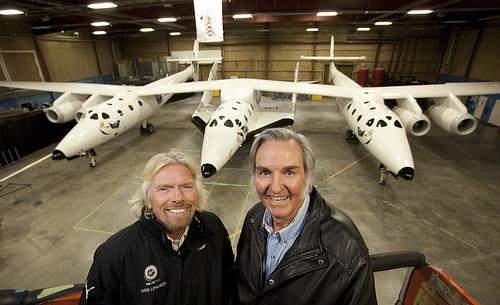 Sir Richard Branson (à esquerda) e Burt Rutan posam para uma foto em frente da SpaceShip2 sob a nave-mãe WhiteKnight2, dento do hangar em Mojave,Ca.