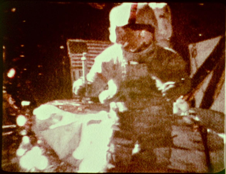 David Scott, comandante da Apollo 15, se prepara para deixar cair um martelo geológico de 1,32 kg e uma pena de falcão de 0,03 kg na Lua.