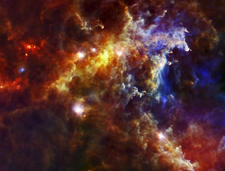 Nebulosa Rosette sob a visão infravermelha do Herschel: esta imagem é uma composição de 3 fotos em diferentes comprimentos de onda. A tonalidade azul mostra a visão de 70 mícrons, em verde temos 160 mícrons e em tons avermelhados 250 mícrons Créditos: ESA/PACS & SPIRE Consortium/HOBYS Key Programme Consortia