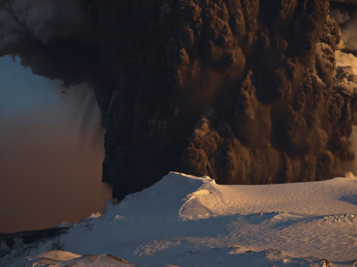 As plumas massivas do vulcão Eyjafjallajokull escondem um helicóptero voando nas proximidades (à esquerda). Crédito: Snaevarr Gudmundsson