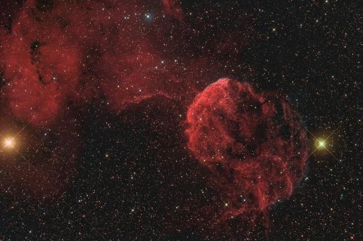 Imagem de campo largo mostra o ambiente da IC 443 (Sharpless 248). Estão visíveis: As estrelas massivas η (direita) e μ (esquerda) Geminorum, a difusa nebulosa de emissão IC444 (Sharpless 249, acima e à esquerda) e a remanescente de supernova G189.6+3.3 (centro). Crédito: Gerhard Bachmayer (abril de 2009) / observatório Gemini