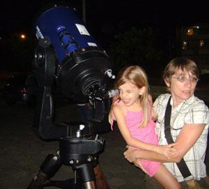 """Luisa esclama: """"Vênus é uma Lua"""", ao observar o planeta no telescópio da UFSC. Crédito da foto: Carolina R. Moraes"""