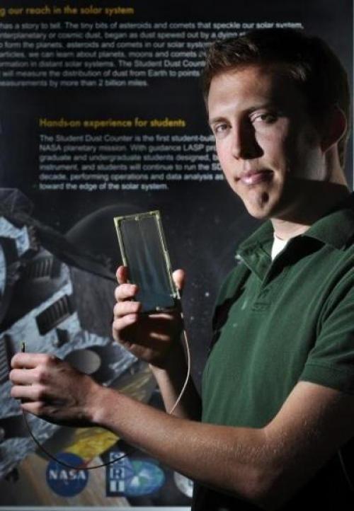 O estudante Andrew Poppe do departamento de física da Universidade da Colorado em Boulder mostra o instrumento SDC. Andrew faz parte de uma equipe de alunos no Laboratório de Física Atmosférica e Espacial que projetou e construiu o Contador de Poeira que foi instalado na espaçonave New Horizons da NASA, que irá explorar Plutão. Crédito: Glenn Asakawa / Universidade do Colorado