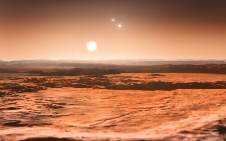 Esta impressão artística mostra uma vista do exoplaneta Gliese 667Cd em direção à sua estrela progenitora (Gliese 667C). Ao fundo à direita podemos ver as estrelas mais distantes deste sistema triplo (Gliese 667A e Gliese 667B). À esquerda no céu está o crescente de um dos outros planetas, o recentemente descoberto Gliese 667Ce. Três planetas deste sistema são super-Terras orbitando em torno da estrela numa região onde a água pode existir sob forma líquida, o que torna estes planetas bons candidatos à presença de vida. Este é o primeiro sistema que se descobre onde a zona habitável se encontra repleta de planetas. Crédito: ESO/M. Kornmesser