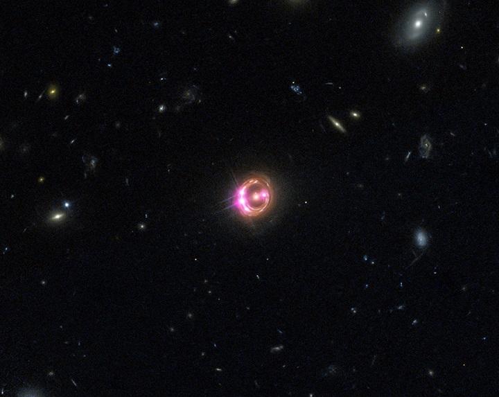 Múltiplas imagens do distante quasar conhecido como RX J1131-1231 são visíveis aqui a partir de  dados combinados a partir do Chandra (em rosa) e do Hubble (vermelho, verde e azul). Créditos: NASA/CXC/Univ of Michigan/R.C.Reis et al; Optical: NASA/STSc