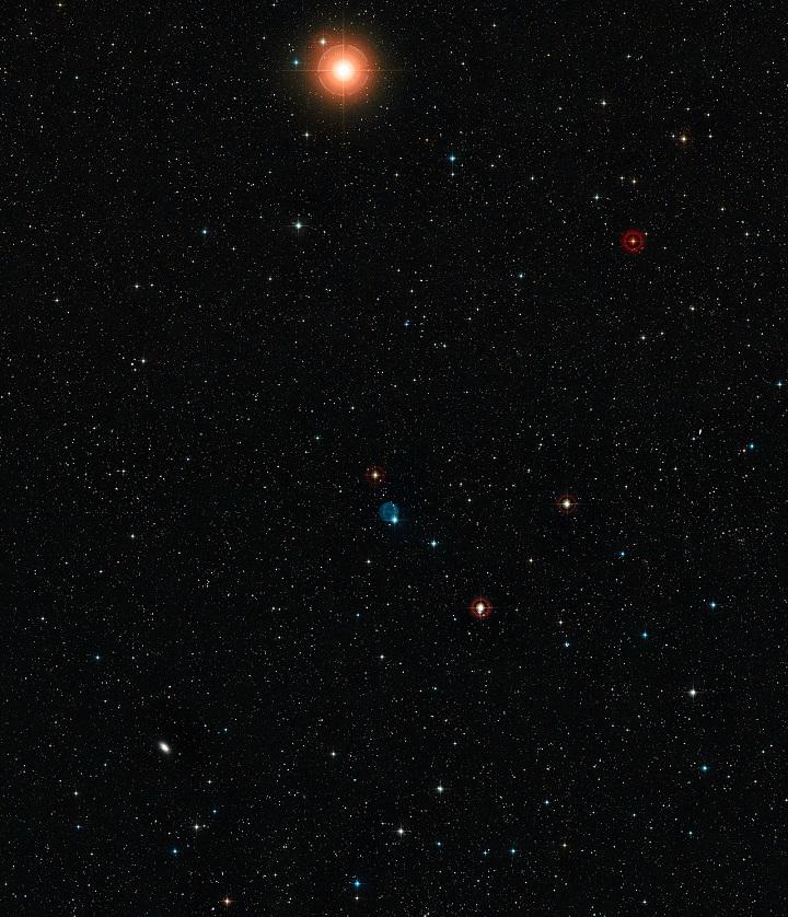 Esta imagem de grande angular mostra o céu em torno da nebulosa planetária Abell 33, que aparece como um círculo azul fantasmagórico próximo do centro. Esta imagem foi criada a partir de material fotográfico do Digitized Sky Survey 2. Podem ver-se também muitas galáxias pouco luminosas e a estrela brilhante cor de laranja na parte superior,  trata-se da Iota Hydri, uma estrela que é suficientemente brilhante para poder ser vista a olho nu. Crédito: ESO/Digitized Sky Survey 2/Acknowledgement: Davide De Martin