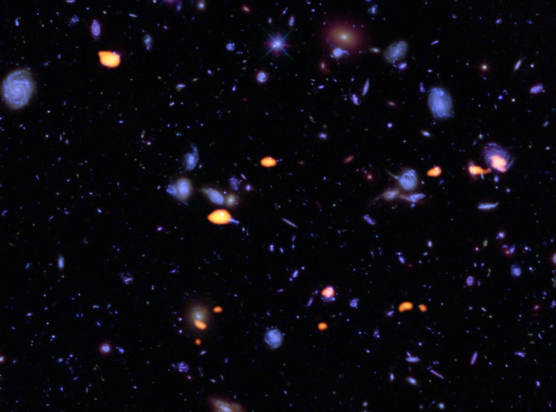 Uma quantidade de galáxias, ricas em monóxido de carbono (o que indica formação potencial de estrelas) foram observadas pelo ALMA (em laranja) no Campo Ultra Profundo do Hubble. As estruturas azuis são galáxias observadas pelo Hubble. Esta imagem baseia-se num rastreio muito profundo do ALMA realizado por Manuel Aravena, Fabian Walter e colegas, que cobriu cerca de um sexto da área total do HUDF. Créditos: B. Saxton (NRAO/AUI/NSF); ALMA (ESO/NAOJ/NRAO); NASA/ESA Hubble